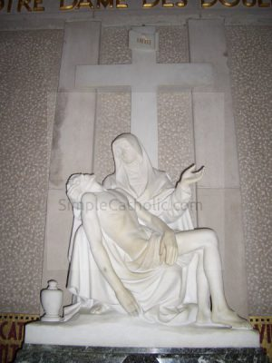 Statue of Mary holding Jesus at the foot of the cross - Simple Catholic